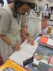 『からだのーと』にサインをする著者の早川ユミさん。
